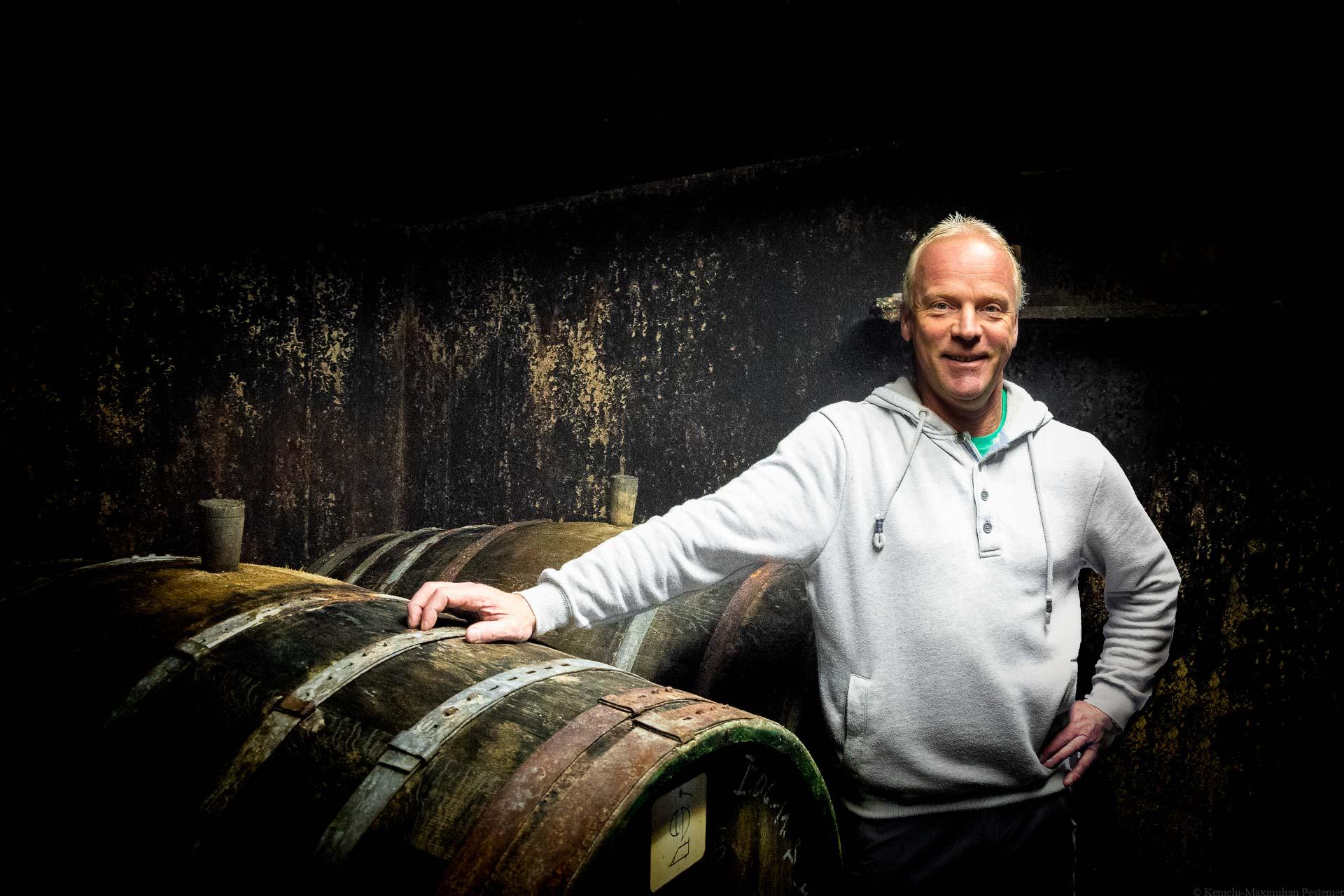 Stefan Erbes steht im Weinkeller des Weingutes Karl Erbes neben alten Weinfässern