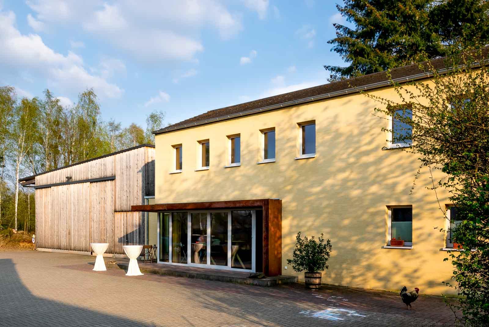 Guthaus des Weingutes Dr. Frey mit Bäumen und Wolken am Himmel.