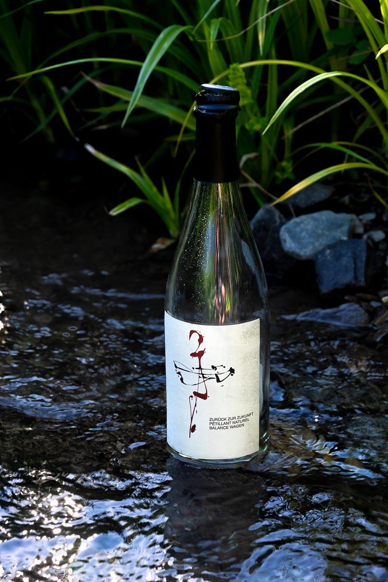 Eine leere Weinflasche des Weinguts Dr. Frey steht mitten in einem Bach.