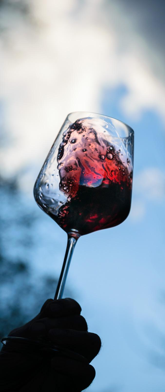 Ein Glas mit Rotwein wird am Abend vorm blauen und bewölkten Himmel geschwenkt.