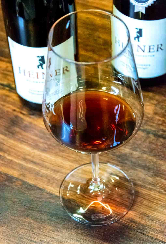 Glas mit Rotwein der Weinmanufakatur Heiner an der Ahr auf Holztisch