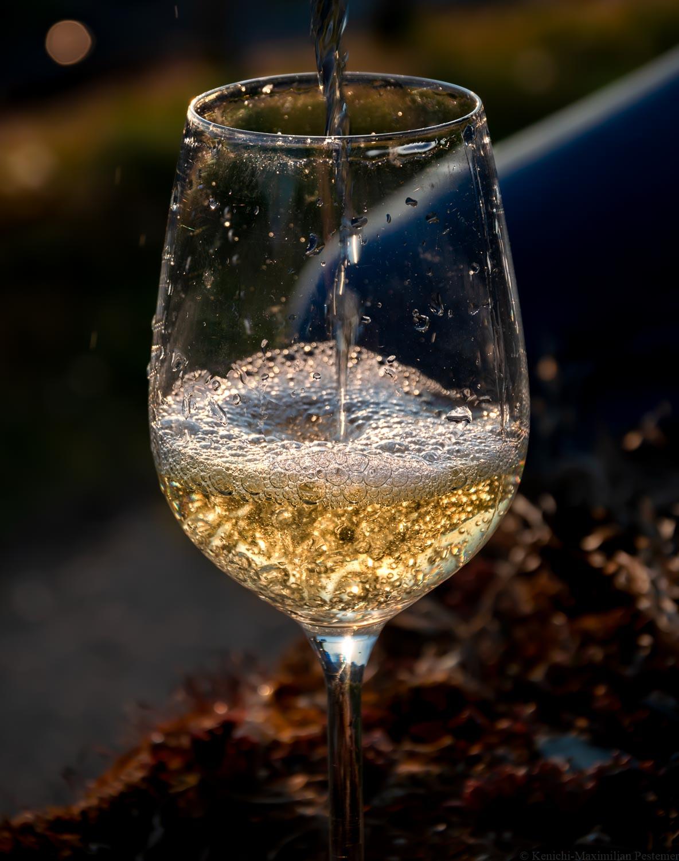 Riesling-Wein wird Abends in ein Glas gegossen