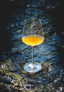 Naturwein und Orangewein im Waldbach an der Dhron: Der Wein Big Bamm von der Tiny Winery befindet sich im Weinglas.