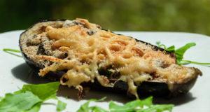 Aubergine mit Käse überbacken auf weißem Teller mit einigen Salatblättern
