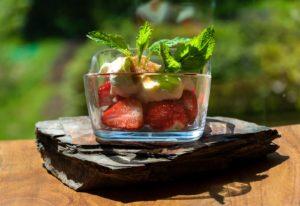 Eine Erdbeer-Nachspeise in einer Glasschüssel befindet sich auf einem Schieferstein und einem Holztisch.