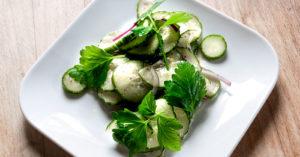 Gurkensalat mit Zwiebeln auf kleinem weißen Teller