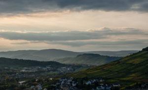 Im Vordergrund befindet sich der Weinbauort Kues. Oberhalb auf der rechten Seite befindet sich der steile Weinberg Kueser Rosenberg. Im Hintergrund fließt die Mosel entlang von weiteren Weinbergen. Am Himmel ist Abendstimmung mit vielen Wolken.