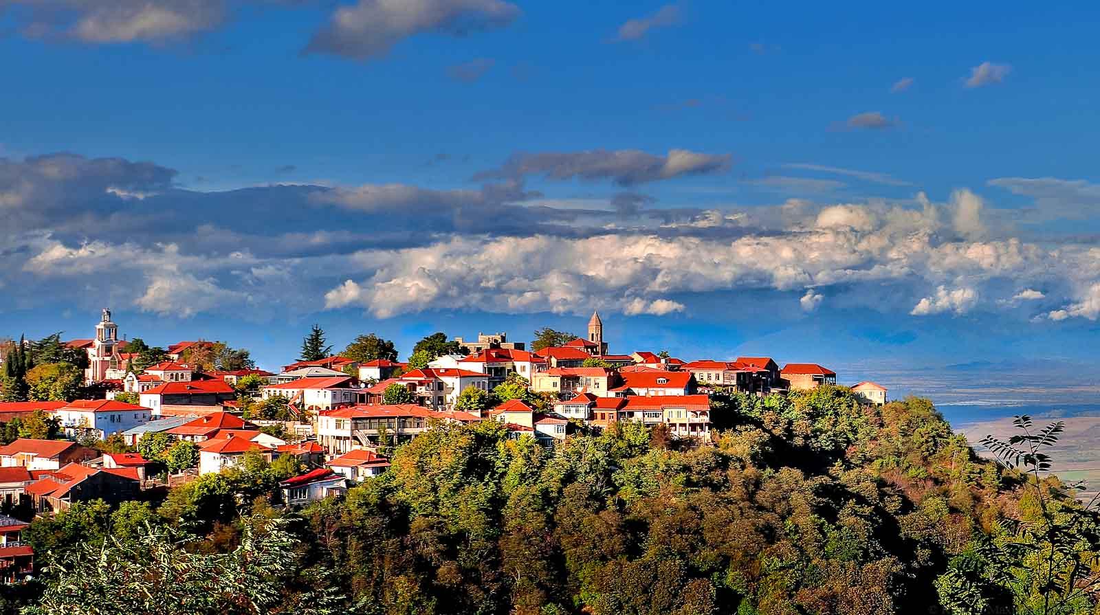 Die georgische Stadt Sighnaghi befindet sich auf einem bewaldeten Berg. Im Hintergrund ist blauer Himmel mit Wolken.