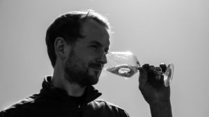 VinVenture Winzer Lukas Bicking mit Weinglas im Weinberg