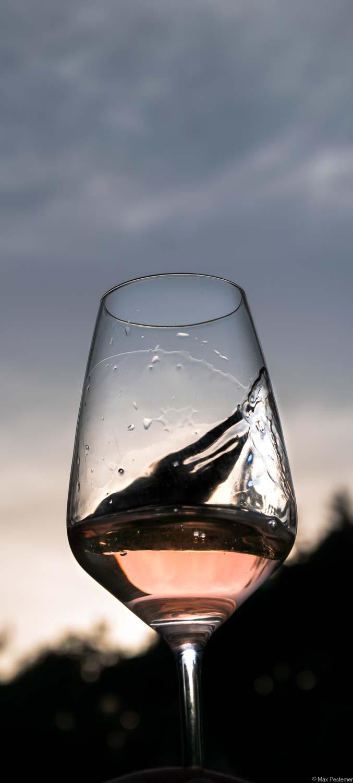 Vinaet-Rosé-Glas wird am späten Abend vor dem Himmel geschwenkt.